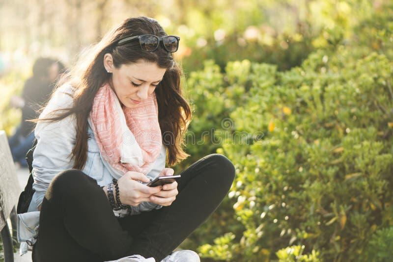 Mujer morena joven que escribe sobre phonek imagen de archivo libre de regalías