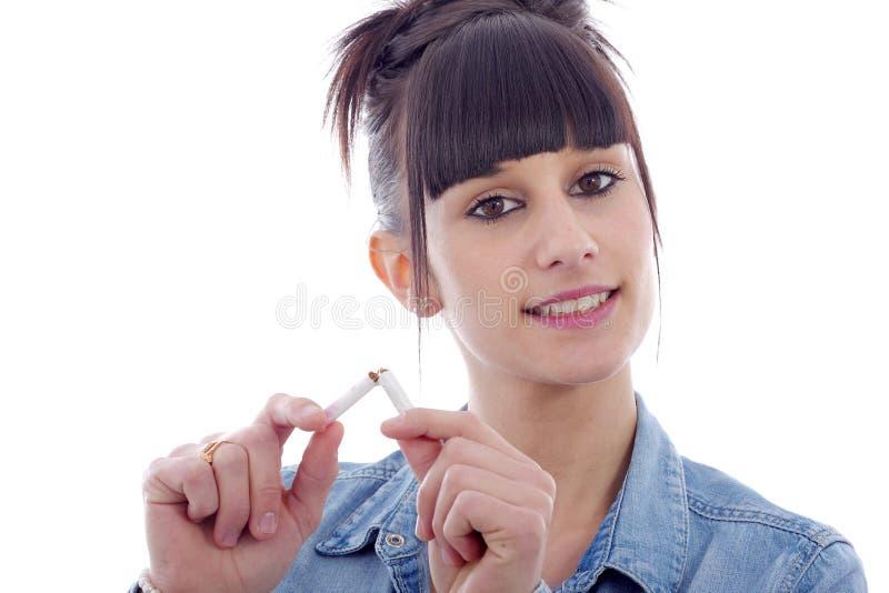 Mujer morena joven que rompe el cigarrillo, concepto de no fumadores foto de archivo