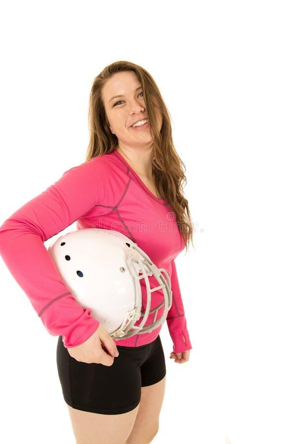 Mujer morena joven que se coloca que sostiene un casco de fútbol americano foto de archivo
