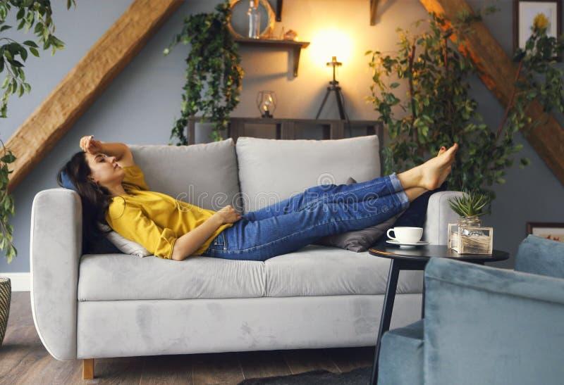Mujer morena joven que se relaja en el sof? despu?s de un d?a largo imagen de archivo libre de regalías