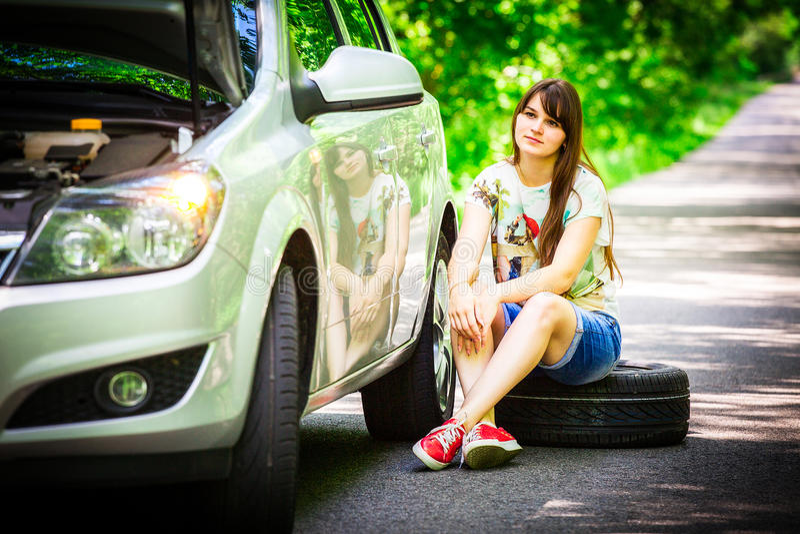 Mujer morena joven que se sienta cerca de un coche de plata en el borde de la carretera con una rueda quebrada imagenes de archivo