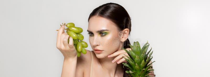 Mujer morena joven sana que mira las uvas verdes en su mano, frutas y verduras en la tabla, foto del estudio encendido foto de archivo