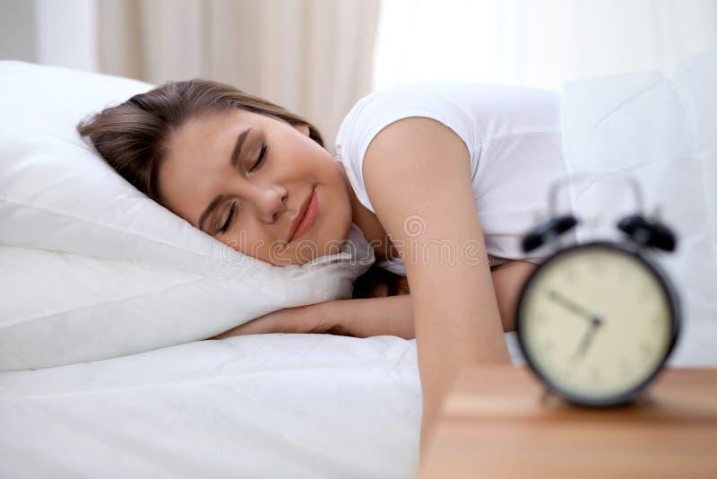 Mujer morena joven soñolienta que estira la mano a la vuelta dispuesta de sonido de la alarma él apagado Despierte temprano, no c imagenes de archivo