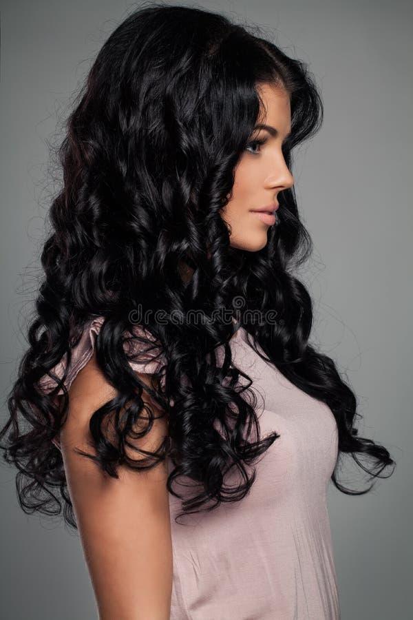 Mujer morena linda con el pelo ondulado fotografía de archivo
