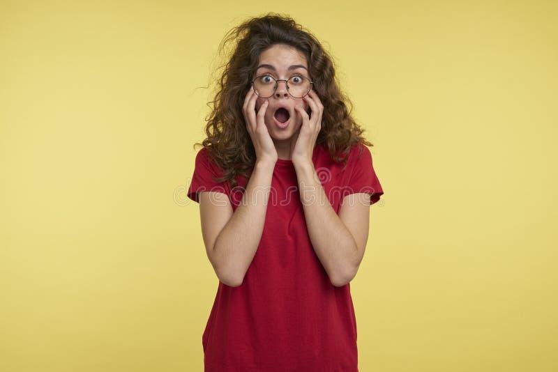 Mujer morena linda con el pelo rizado y las lentes en la camiseta roja, abierta su boca en una sorpresa, contra amarillo fotografía de archivo