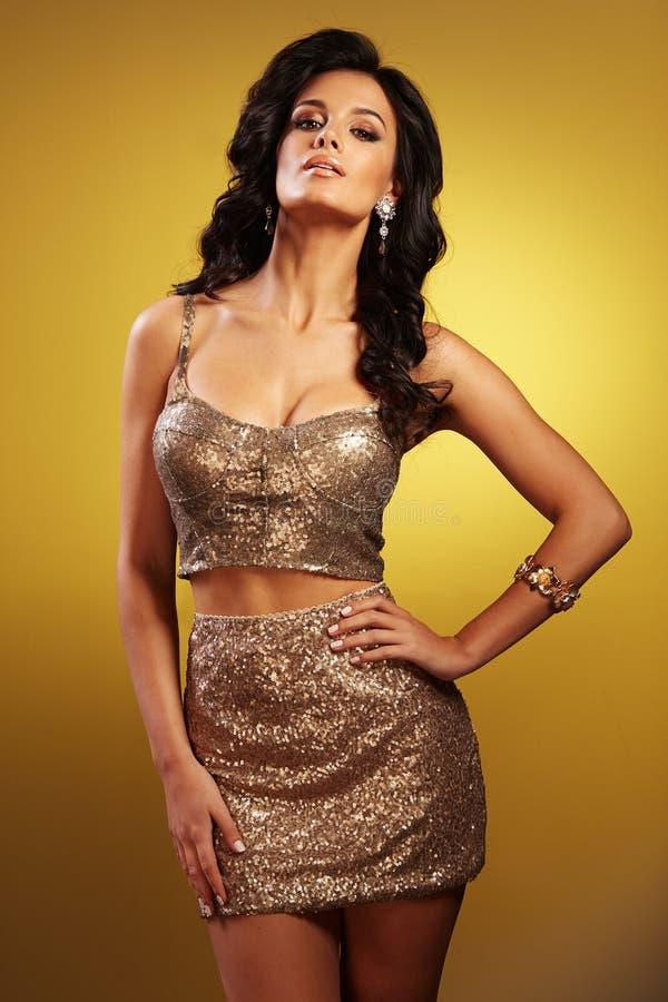 Mujer morena magnífica con el pelo largo en falda y bustiere con las lentejuelas de oro foto de archivo