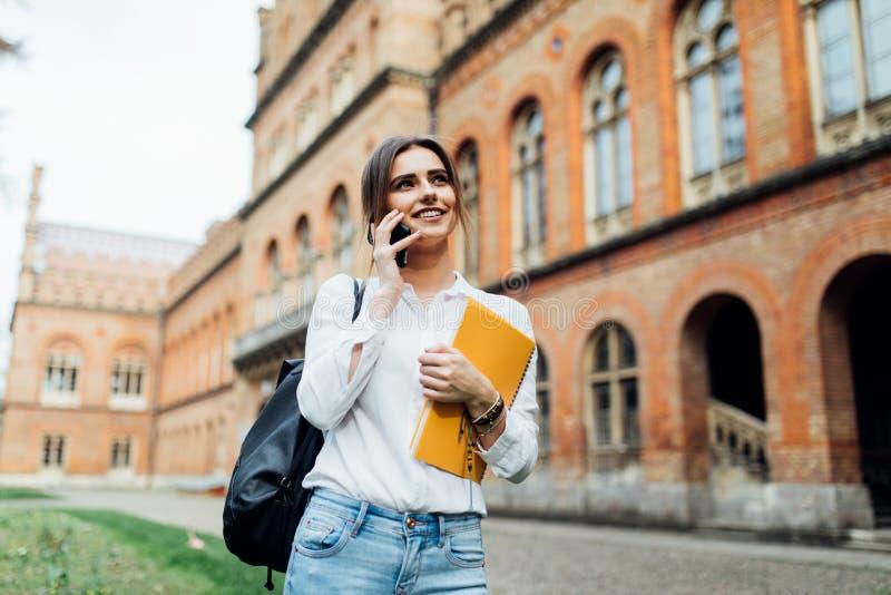 Mujer morena positiva en la ropa de sport que tiene conversación móvil en el campus con el libro el día soleado Muchacha bonita s fotos de archivo libres de regalías