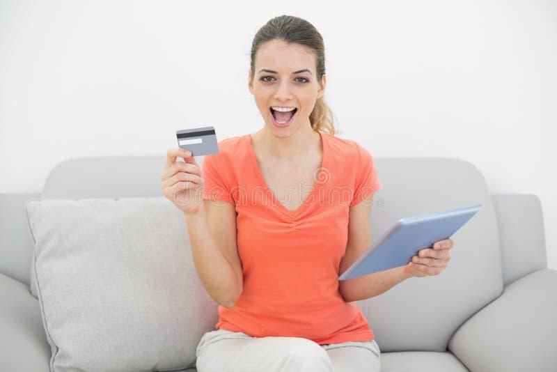 Mujer morena que anima que muestra su tarjeta de crédito que sostiene su tableta imagen de archivo