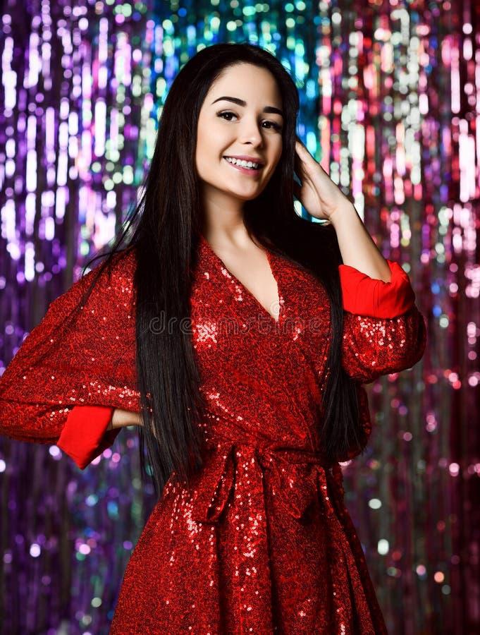 Mujer morena que celebra, divirtiéndose en la fiesta Retrato de una muchacha sonriente feliz en un vestido rojo brillante atract fotos de archivo libres de regalías