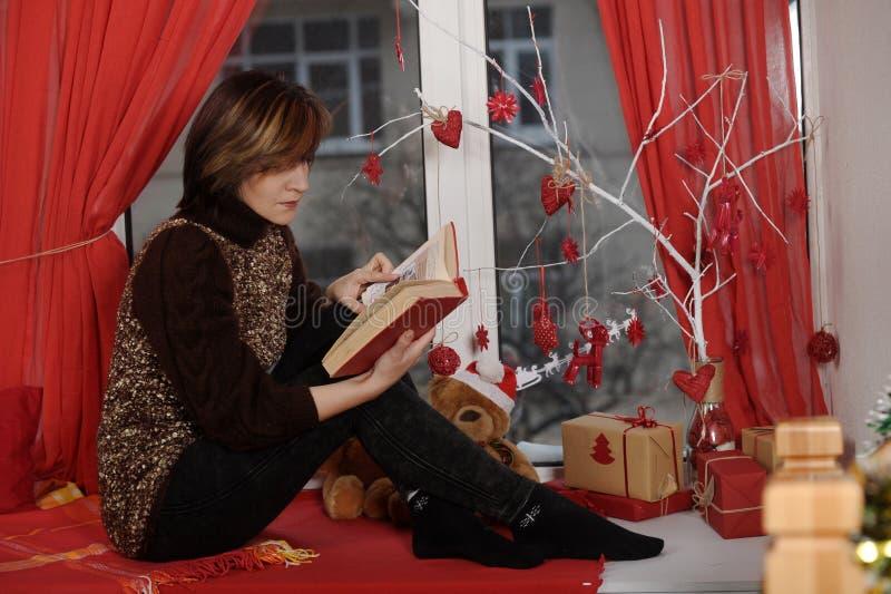 Mujer morena que lee un libro en el alféizar en la Navidad tim imagenes de archivo