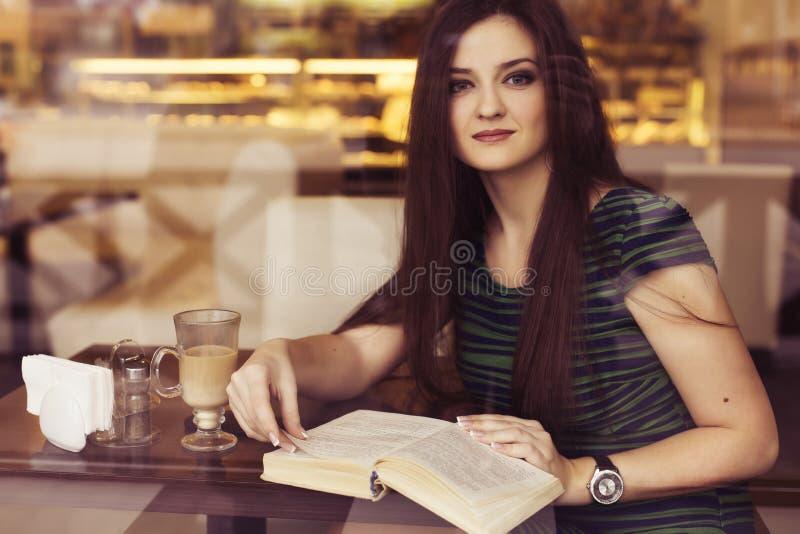 Mujer morena que se sienta en el café del libro de lectura del café, el studing y de la consumición fotografía de archivo