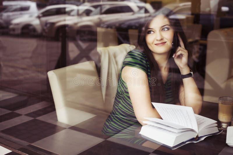 Mujer morena que se sienta en el café del libro de lectura del café, el studing y de la consumición y hablando en el teléfono imágenes de archivo libres de regalías