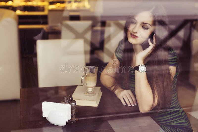 Mujer morena que se sienta en el café del libro de lectura del café, el studing y de la consumición y hablando en el teléfono fotografía de archivo