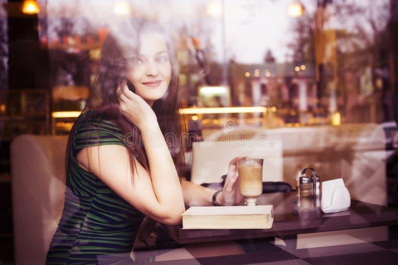 Mujer morena que se sienta en el café del libro de lectura del café, el studing y de la consumición y hablando en el teléfono imagen de archivo
