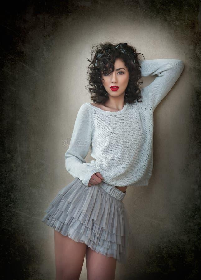 Mujer morena rizada joven encantadora en falda corta del cordón y la blusa blanca que se inclinan contra la pared Mujer joven mag imagen de archivo