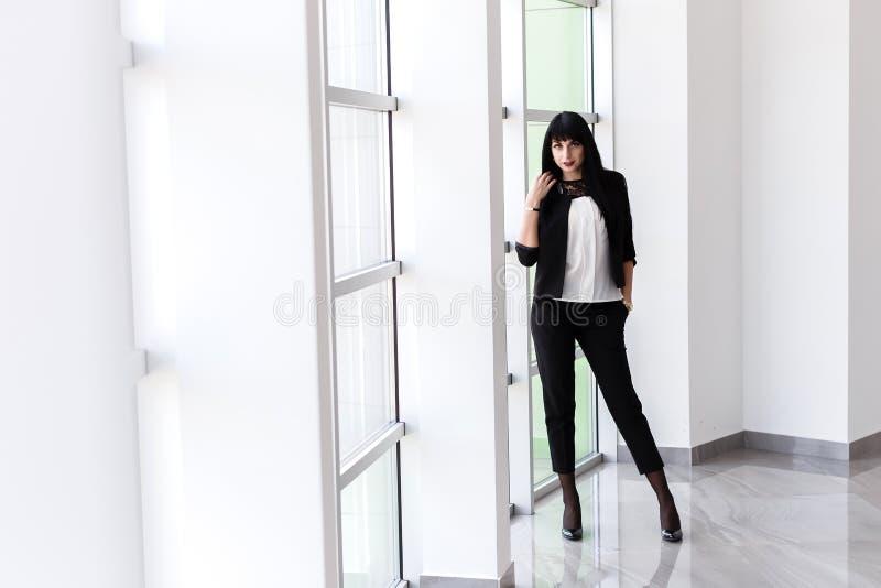 Mujer morena seria atractiva joven vestida en una situación negra del traje de negocios cerca de la ventana en la oficina, mirand imágenes de archivo libres de regalías