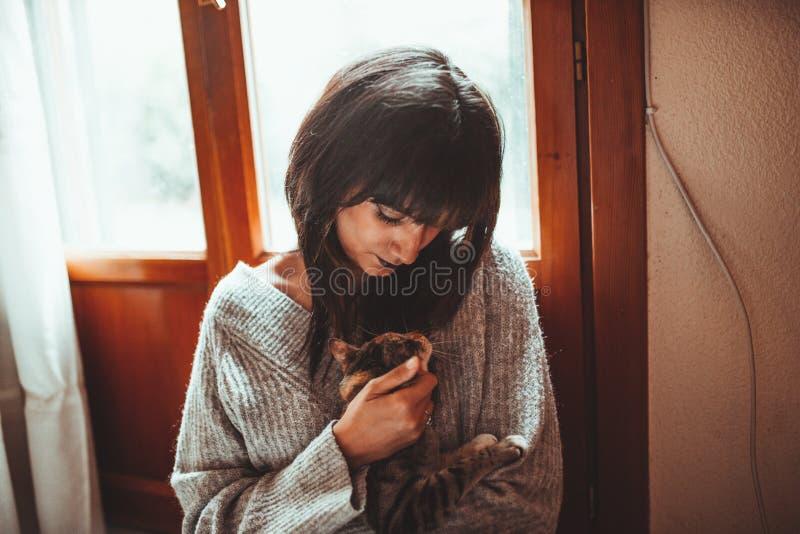 Mujer morena seria joven que sostiene un gatito del gato atigrado fotos de archivo