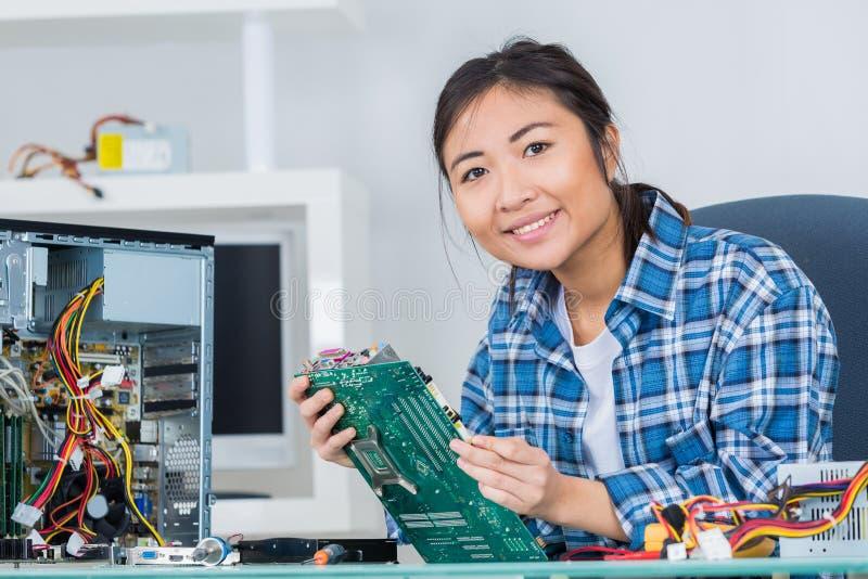 Mujer morena sonriente del ingeniero de la reparación del ordenador en el trabajo imágenes de archivo libres de regalías