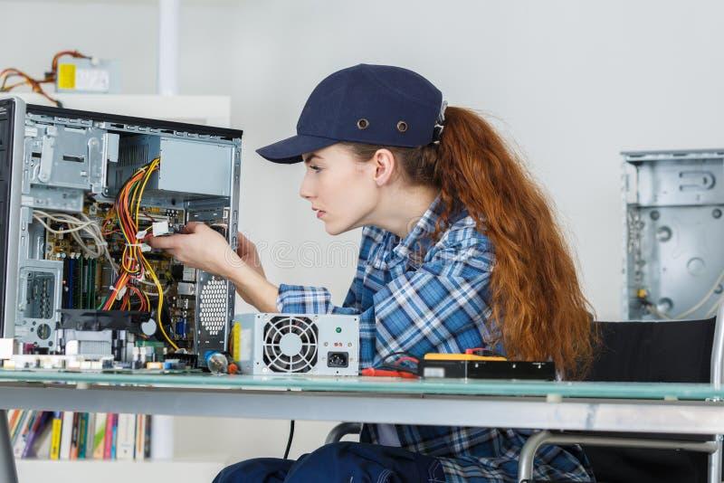 Mujer morena sonriente del ingeniero de la reparación del ordenador en el trabajo fotografía de archivo libre de regalías