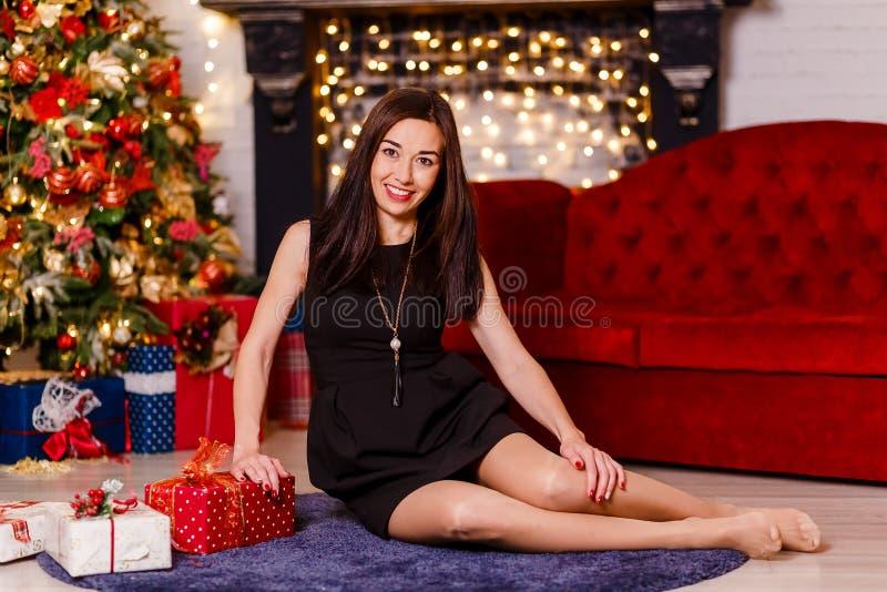 Mujer morena sonriente en el vestido negro corto que se sienta en el piso imagen de archivo libre de regalías