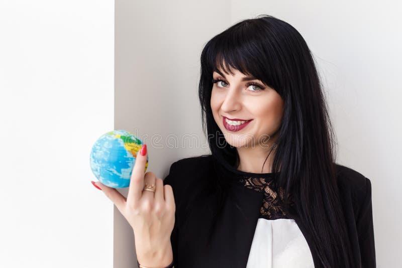 Mujer morena sonriente hermosa joven vestida en el traje de negocios negro que sostiene un globo de la tierra del planeta concept fotos de archivo libres de regalías