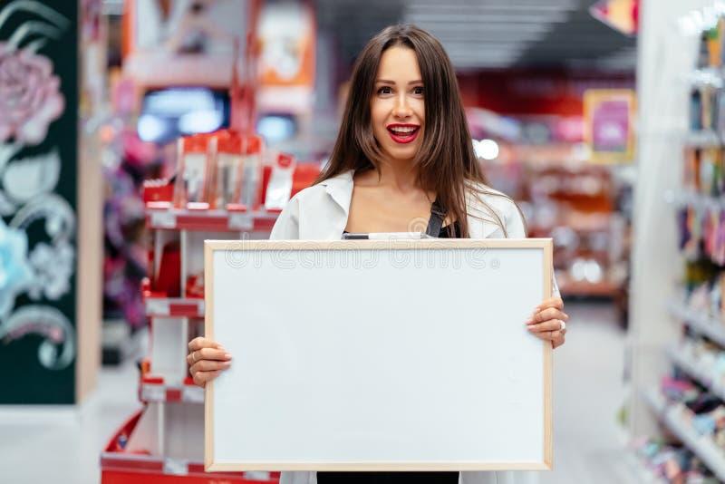 Mujer morena sonriente que lleva a cabo al tablero en blanco blanco fotografía de archivo