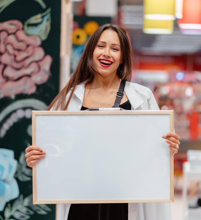 Mujer morena sonriente que lleva a cabo al tablero en blanco blanco imágenes de archivo libres de regalías