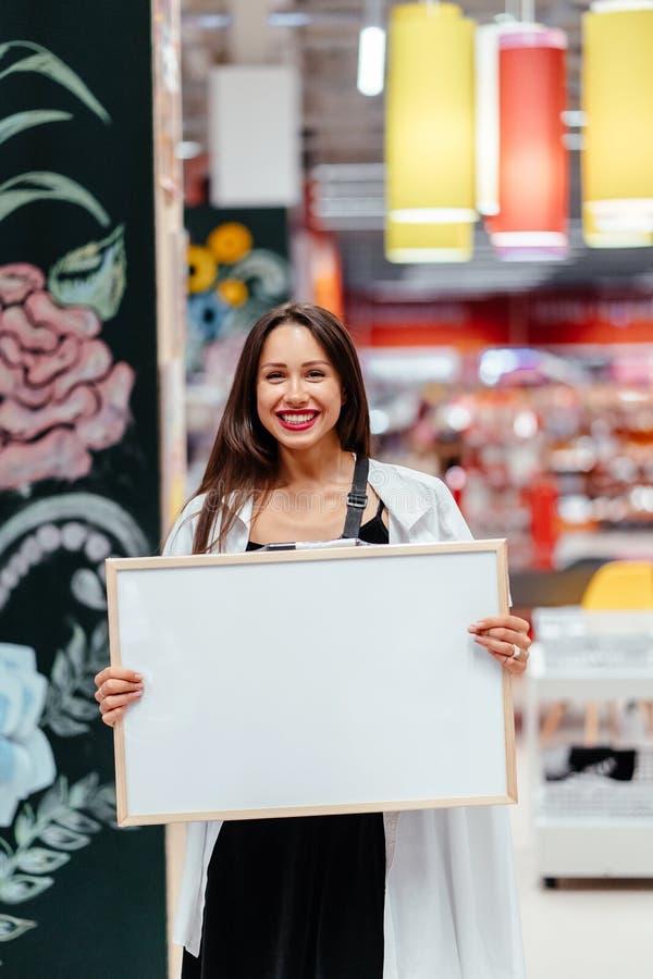 Mujer morena sonriente que lleva a cabo al tablero en blanco blanco fotos de archivo