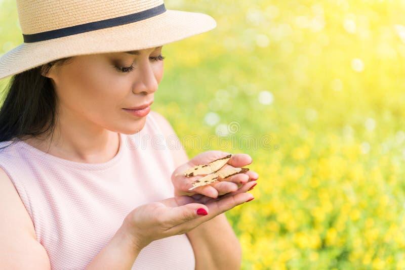 Mujer morena tranquila con la mariposa en prado fotografía de archivo libre de regalías