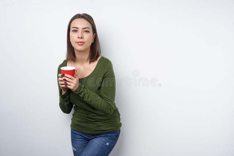 Mujer morena tranquila que sostiene la taza de papel disponible imagenes de archivo