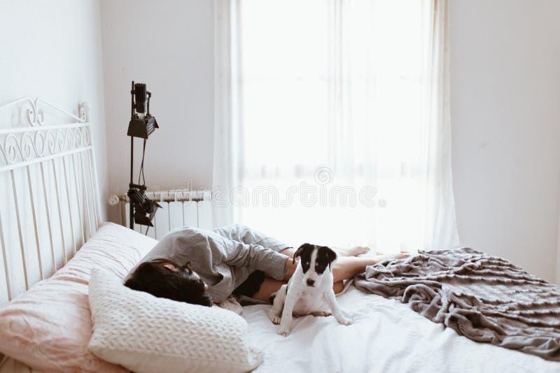 Mujer morena triste joven que acaricia su perrito de Labrador que miente en dormitorio imagen de archivo