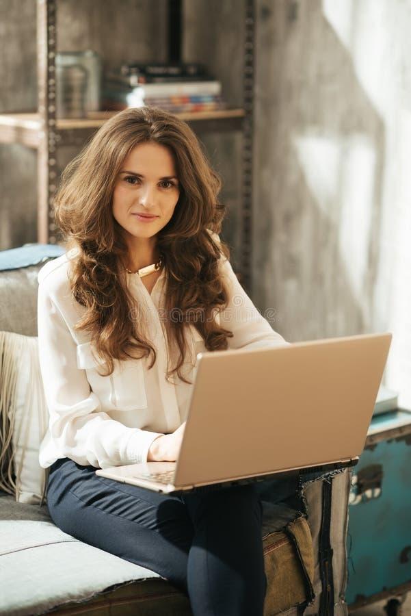 Mujer morena vestida elegante que trabaja en el ordenador portátil en el apartamento del desván imagenes de archivo