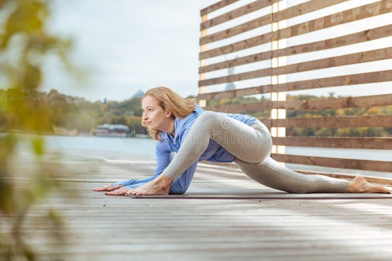 Mujer motivada joven que practica estirando los ejercicios al aire libre imagen de archivo