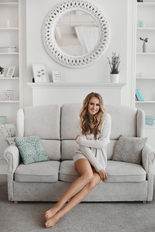 Mujer moza longitudinal con el largo pelo rubio y suéter blanco sentado en el sofá en una acogedora sala de estar por la mañana imagen de archivo libre de regalías