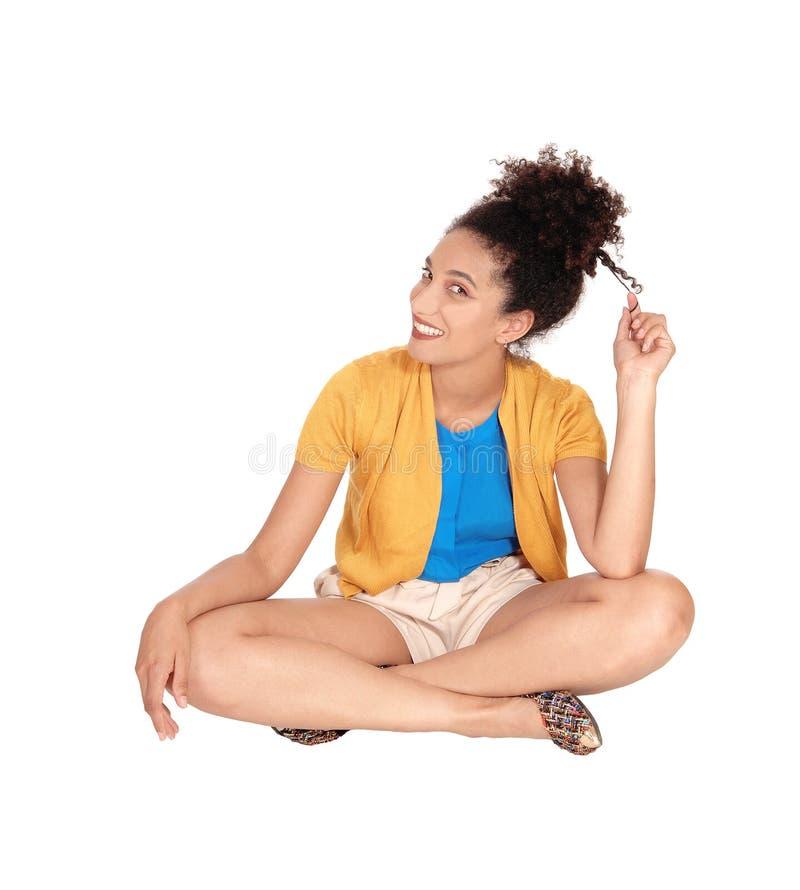 Mujer multirracial joven hermosa que se sienta en piso foto de archivo