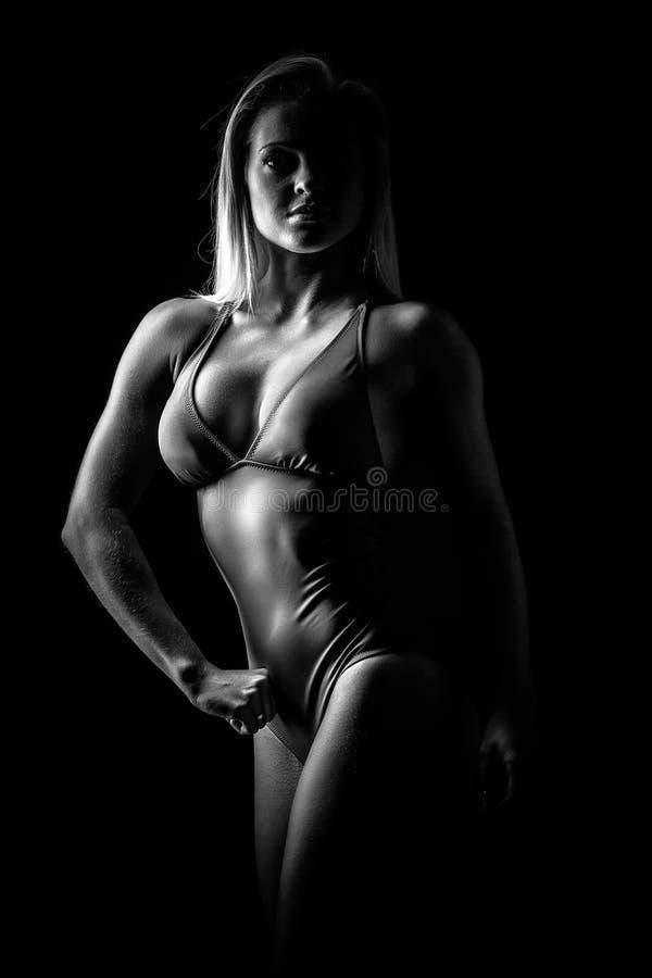 Mujer muscular aislada contra fondo negro fotos de archivo libres de regalías