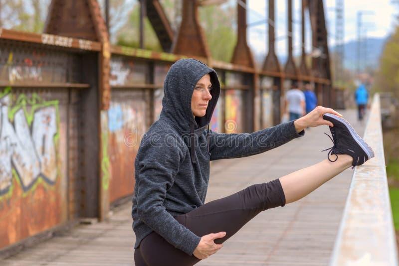 Mujer muscular apta que hace estirando ejercicios imagenes de archivo