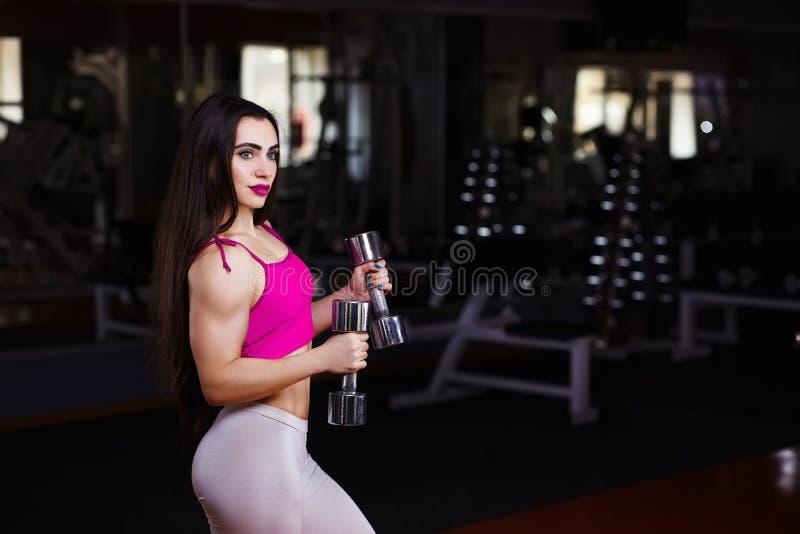 Mujer muscular atractiva joven de la aptitud que hace ejercicio con mudo fotografía de archivo