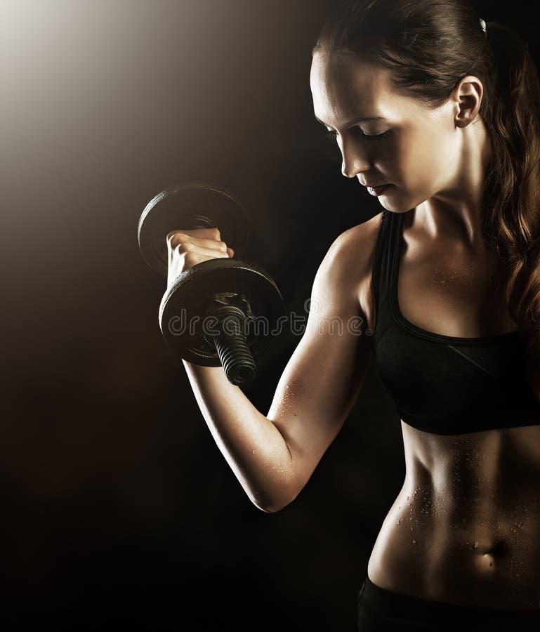 Mujer muscular de la aptitud que se resuelve con pesas de gimnasia imagenes de archivo