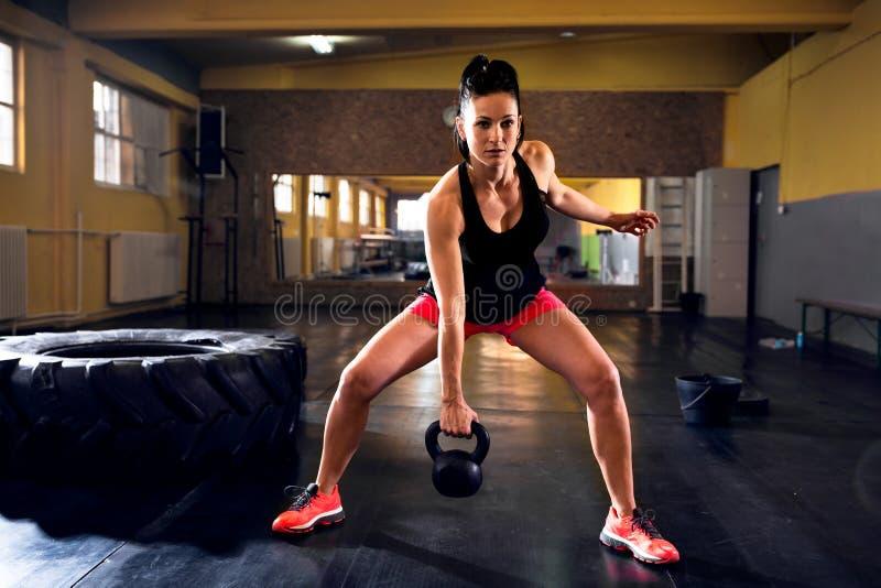 Mujer muscular del ajuste que hace entrenamiento con el kettlebell en Rus foto de archivo libre de regalías