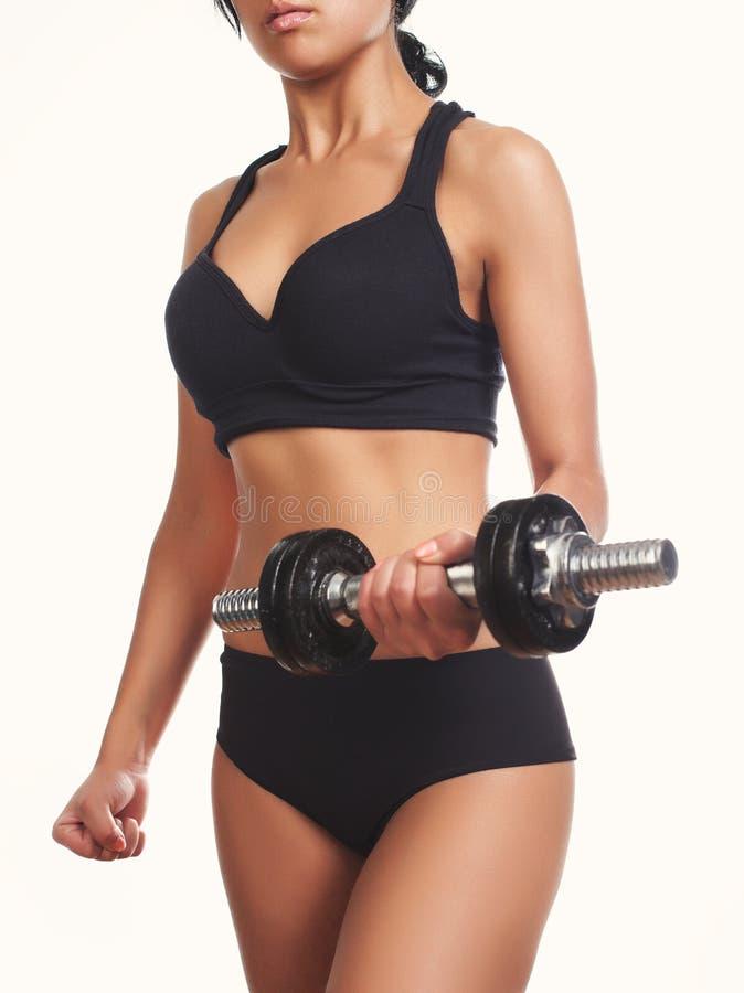 Mujer muscular deportiva hermosa que se resuelve con pesa de gimnasia fotografía de archivo libre de regalías