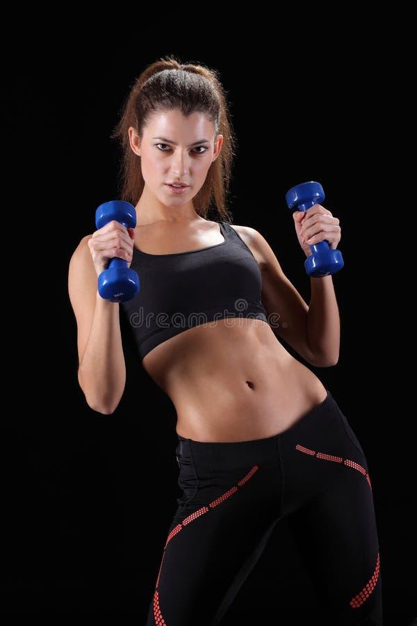 mujer muscular deportiva que se resuelve con pesas de gimnasia fotografía de archivo libre de regalías