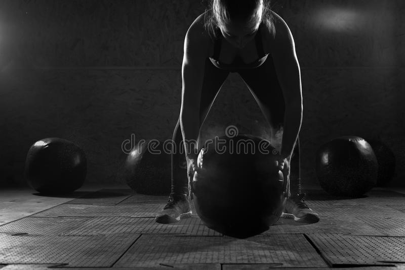 Mujer muscular joven que ejercita con la bola pesada imagenes de archivo