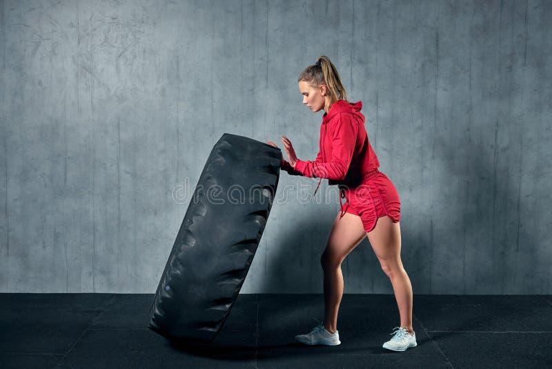 Mujer muscular joven que mueve de un tirón un neumático en el entrenamiento duro con el instructor personal en el gimnasio del ga imagenes de archivo