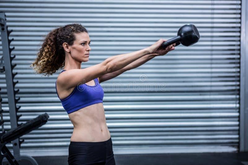 Mujer muscular que ejercita con el kettlebell fotos de archivo