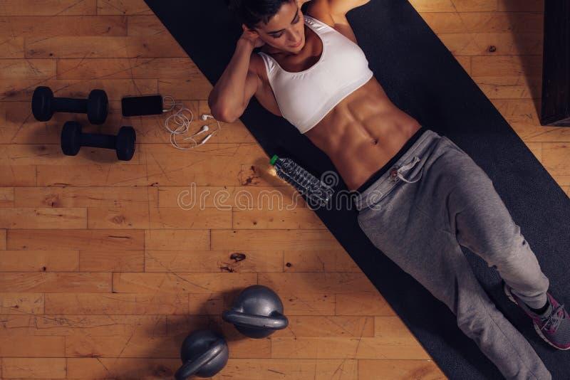 Mujer muscular que hace entrenamiento del ABS en gimnasio fotos de archivo