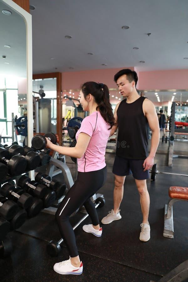 Mujer muscular que se resuelve en el gimnasio que hace ejercicios con pesas de gimnasia en los bíceps, ABS desnudo masculino fuer fotos de archivo libres de regalías