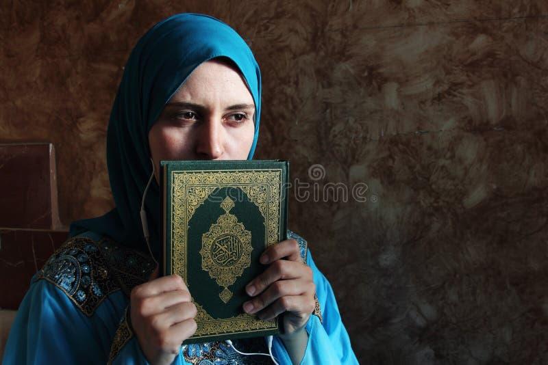 Mujer musulmán árabe con el libro sagrado y las auriculares islámicos del Corán fotos de archivo