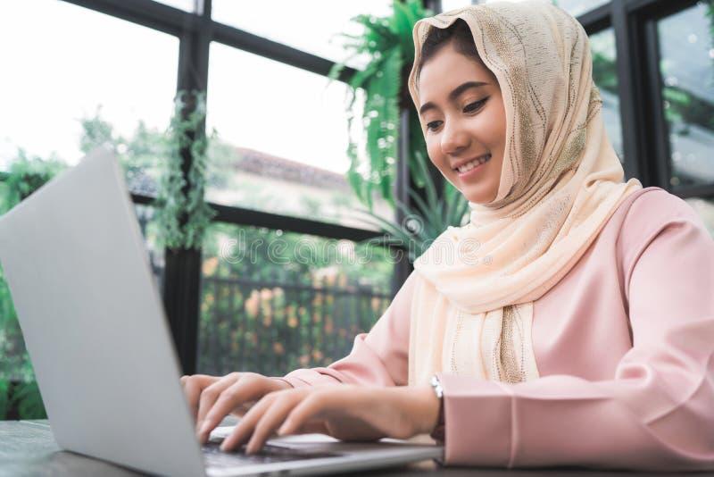 Mujer musulmán asiática sonriente de los jóvenes hermosos que trabaja en el ordenador portátil que se sienta en sala de estar en  fotos de archivo