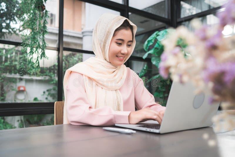 Mujer musulmán asiática sonriente de los jóvenes hermosos que trabaja en el ordenador portátil que se sienta en sala de estar en  foto de archivo